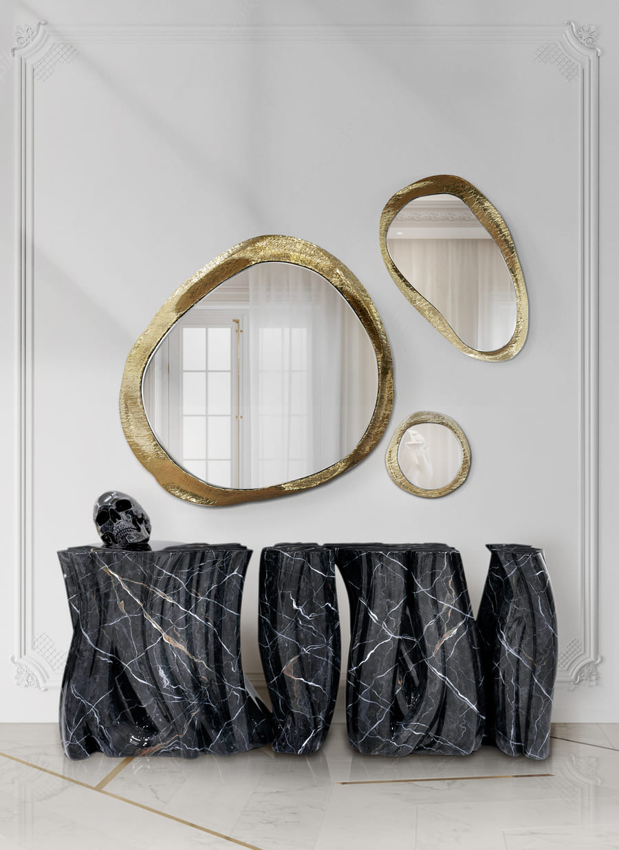A luxurious entryway with a black marble console and gold mirrors.