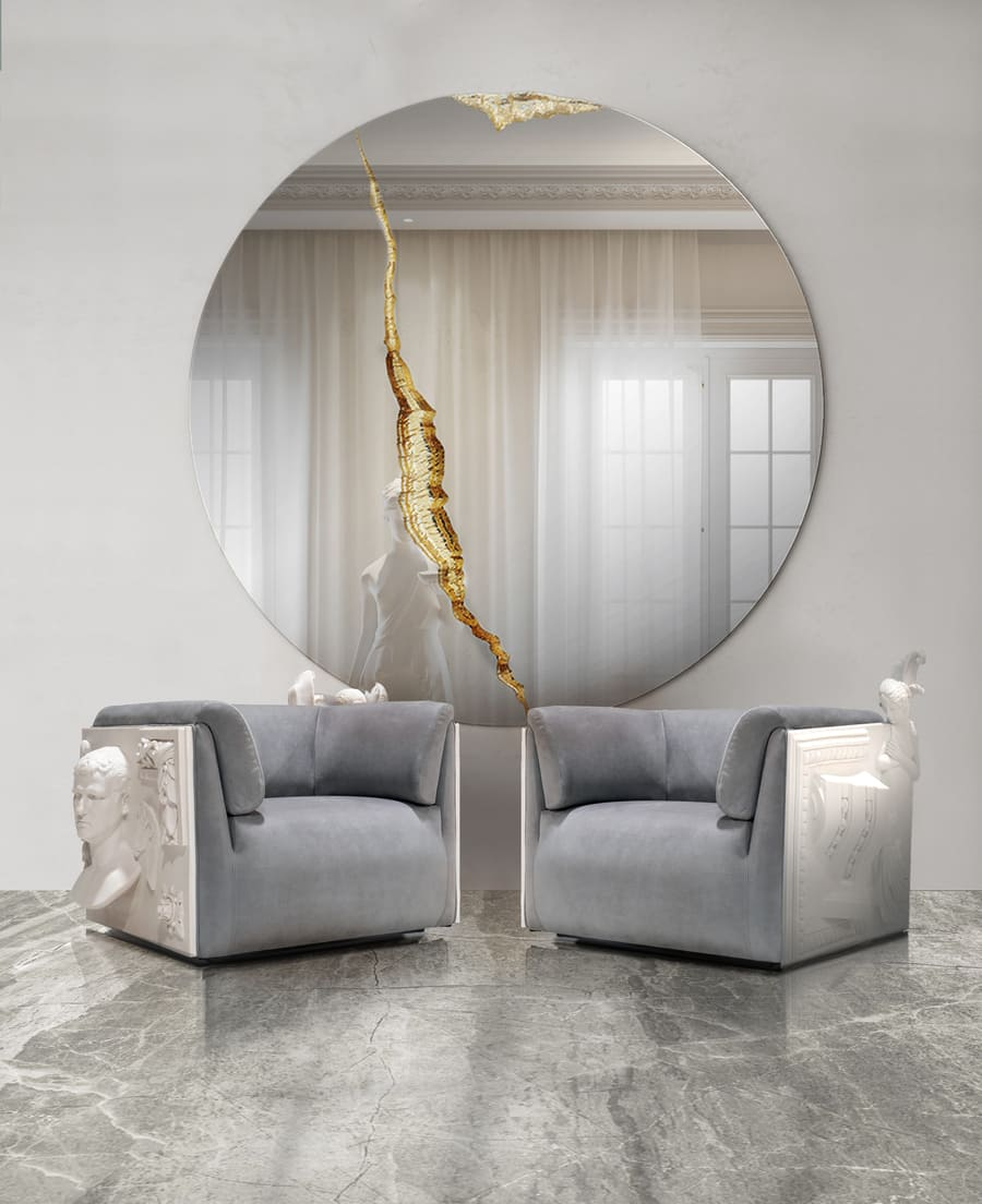 A luxurious living room with a gold mirror and white and grey armchairs.